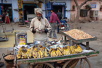 Bharatpur, Rajasthan, India.  Old Man Selling Bananas and Peanuts in a Roadside Stand.