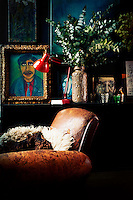 A well worn brown leather armchair stands in front  of a collection of ornaments, paintings, a red angle-poise lamp and a foliage arrangement, which are displayed on a sideboard