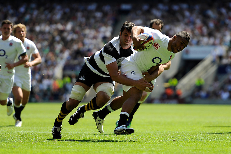 Kyle Eastmond of England forces his way through the tackle attempt by Marco Wentzel of the Barbarians to score a try during the match between England and Barbarians at Twickenham on Sunday 26th May 2013 (Photo by Rob Munro)