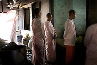 The head bhikkhuni nuns watch over prayers before lunch at a monastery in Mandalay. Buddhist nuns are not treated with the same reverence as their male counterparts, having to prepare their own food, and living in monasteries that are often pushed to the outskirts of town. The monasteries themselves are usually less well kept than the monks' monasteries due to a lack of funds..