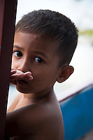 A village that is flooded during the Monsoon Season near the Tonle Sap Lake, Cambodia Portrait of a young boy on a boat on the Tonle Sap Lake,