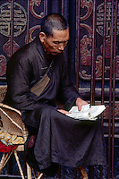 CHINESE MONK reads a PRAYER BOOK at the Buddhist YUANTONG TEMPLE in KUNMING - YUNNAN, CHINA