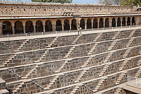 Two Young Boys Looking into the Chand Baori Step Well, Abhaneri Village, Rajasthan, India.  Built 800-900A.D.