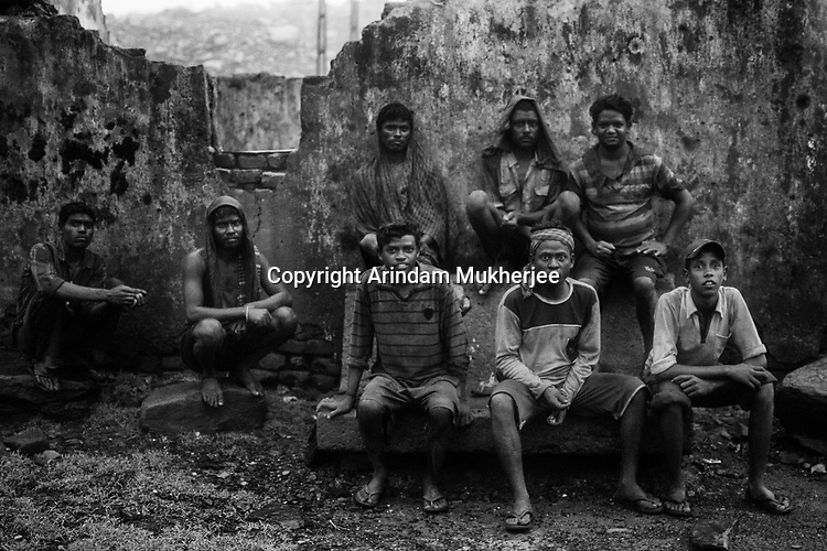 Men are resting after coming back from work at Laltenganj. These are the few people still to be rehabilated. Laltenganj slum is one of the most affected areas by coal mine fire. A huge coal mine fire is engulfing the city of Jharia from all its sides. All scientific efforts have gone in vain to stop this raging fire. This fire is affecting lives of people living in and around Jharia. Jharkhand, India. Arindam Mukherjee
