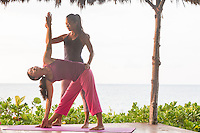 Yoga instructor Miki Sato assists a student with the triangle yoga asana on a Hawaiian beach.