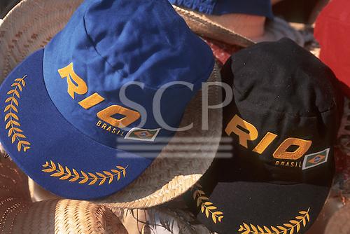 "Rio de Janeiro, Brazil. ""Rio"" baseball caps and straw hats; black, purple - tourist souvenirs."