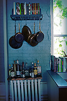 Copper frying pans hanging from a small shelf with books on above bottles of drink displayed on a wooden shelf above a retro radiator.