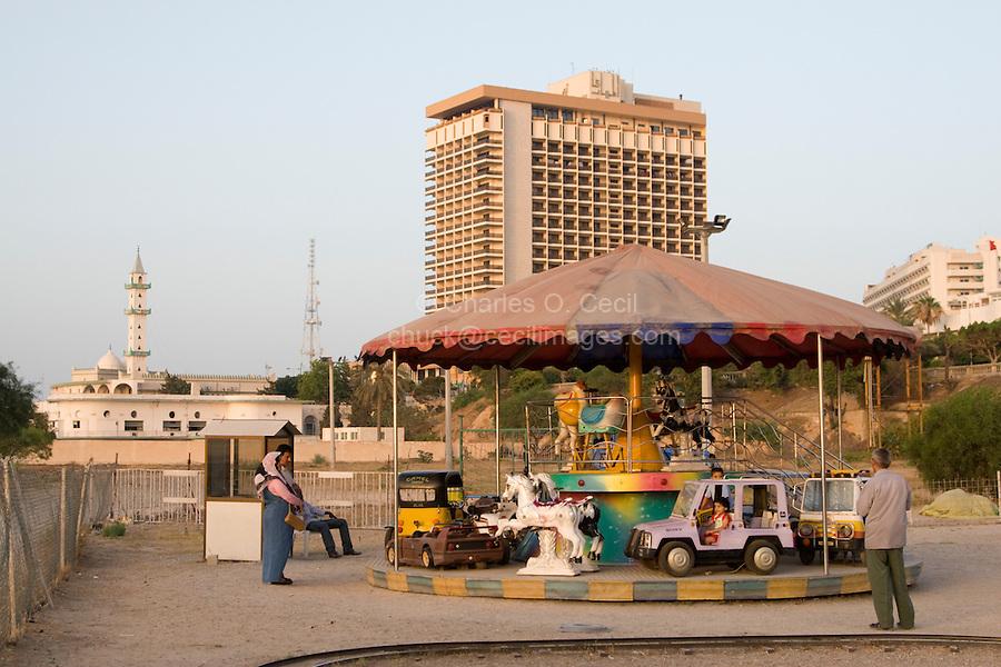 Tripoli, Libya, North Africa - Libyan Parents Watching Child on Amusement Park Ride.