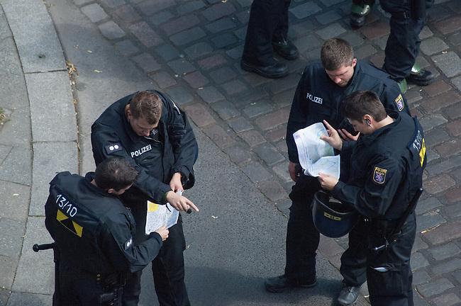 """Polizei sperrt Teil von Kreuzberg wegen Protest gegen die Raeumung der Gerhard-Hauptmann-Schule in der Ohlauer Strasse.<br /> Am 24. Juni 2014 hat der Gruene Bezirksstadtrat von Berlin-Kreuzberg, Hans Panhoff die Raeumung der """"Fluechtlingsschule"""" angeordnet. Zu dieser offiziell als """"Umzug geschoenten Raeumung war die Polizei mit gezogenen Maschinenpistolen angerueckt, hatte jedoch noch keinen Auftrag zur Raeumung. Etliche Fluechtlinge verbarrikadierten sich in dem Schulgebaeude und fluechteten auf das Dach.<br /> Die Polizei hat seit dem 24. Juni mit ueber 1.000 Beamten saemtliche Strassen um die Schule abgeriegelt. Anwohner duerfen nur nach Personalienfeststellung in ihre Wohnungen, Geschaefte und Gewerbe koennen keine Kundschaft mehr empfangen. Anwohner die gegen das Vorgehen der Polizei protestieren werden von Beamten drangsaliert, geschlagen und verletzt. Mehrere Personen, darunter auch Kinder mussten zum Teil mit Kieferbruch ins Krankenhaus. Die Personalien der Pressevertreter werden ohne Angabe von Gruenden erfasst, Dienstnummern werden verweigert.<br /> Am 1. Juli 2014 hat Baustadtrat Panhoff die polizeiliche Raeumung des Schulgebaeudes beantragt. Einige der Fluechtlinge haben angekuendigt, im Fall der Raeumung vom Dach zu springen. """"Wir haben nichts mehr zu verlieren!"""" sagen sie.<br /> Im Bild: Beamte aus Hessen studieren Umgebungskarten und Anfahrtsplaene im Zusammenhang mit der Raeumung der Schule.<br /> 2.7.2014, Berlin<br /> Copyright: Christian-Ditsch.de<br /> [Inhaltsveraendernde Manipulation des Fotos nur nach ausdruecklicher Genehmigung des Fotografen. Vereinbarungen ueber Abtretung von Persoenlichkeitsrechten/Model Release der abgebildeten Person/Personen liegen nicht vor. NO MODEL RELEASE! Don't publish without copyright Christian-Ditsch.de, Veroeffentlichung nur mit Fotografennennung, sowie gegen Honorar, MwSt. und Beleg. Konto: I N G - D i B a, IBAN DE58500105175400192269, BIC INGDDEFFXXX, Kontakt: post@christian-ditsch.de<br /> Urhebervermerk wi"""