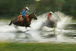 Two cowboys or vaqueros splash through water on their horses.