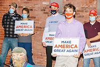 Audience members wear facemasks and hold Make America Great Again signs while Eric Trump, son of US president Donald Trump, speaks during a Make America Great Again! campaign rally at the DoubleTree by Hilton Manchester Downtown in Manchester, New Hampshire, on Mon., Oct. 19, 2020. The audience chairs are distanced to follow safety protocols during the ongoing Coronavirus (COVID-19) global pandemic, just a few weeks after Donald Trump himself contracted the disease, though many other Trump campaign events are lax about COVID safety protocols.