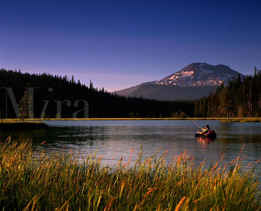 Distant view of a fly fisherman at dusk on Hosmer Lake. Oregon.