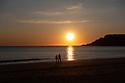Two people enjoy the winter sunset on the beach (Praia da California) in Sesimbra, Portugal.