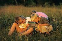 Kinder beobachten gefangene Heuschrecken, Heuschrecke in einem Terrarium, Wiese