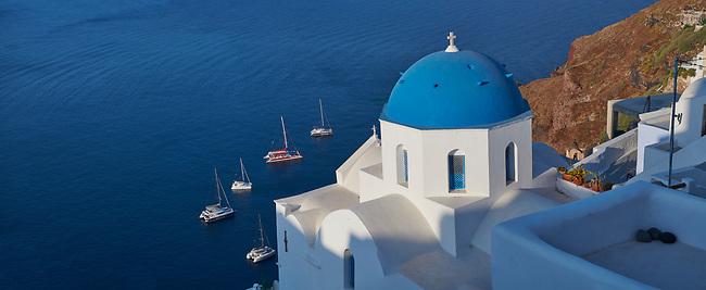 Panoramic view of traditional blue domed Greek Orthodox church of Oia, Island of Thira, Santorini, Greece.