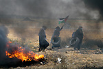 Palestinian women carry tires during clashes with Israeli security forces in tents protest where Palestinians demanding the right to return to their homeland, at the Israel-Gaza border, in Khan Younis in the southern Gaza Strip, on May 4, 2018. Photo by Yasser Qudih