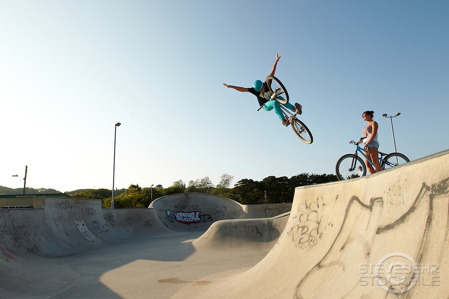 Clinton Johns riding DMR jump bike , with girlfriend Georgina watching .  Hayle skatepark, Cornwall .