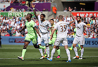 Kelechi Iheanacho of Manchester City (L) celebrates his opening goal as Swansea players protest to the linesman for an offside during the Swansea City FC v Manchester City Premier League game at the Liberty Stadium, Swansea, Wales, UK, Sunday 15 May 2016