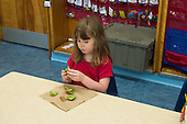 MR / Schenectady, NY. Zoller Elementary School (urban public school). Kindergarten classroom. Girl (6) with fresh fruit (a kiwi) at snack time. Fresh fruit is provided by a special program called FFVP (Fresh Fruit and Vegetable Program) This is a New York State funded program to provide a variety of fresh fruits and vegetables as snacks free of charge to all enrolled students in participating schools. The program is for children in elementary schools with a high percentage of students receiving free and reduced price lunches. MR: Bin1. ID: AM-gKw. © Ellen B. Senisi.