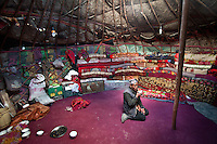 The interior of a yurt with a man drinking tea..Blankets filled with yak and sheep wool pile up against the inside wall of the yurt to insulate it from the constant winds. The floor carpet - bartered against 2 sheep - was acquired by Toorsoon in the lower valleys of Pakistan, a 10 days round trip leading over a 5000m pass. The wooden poles - over hundred years old - are handed over, generation after generation...At the Kyrgyz settlement of Bozoi Gumbaz, before Chaqmaqtin lake, Amon Boi's camp...Trekking through the high altitude plateau of the Little Pamir mountains (average 4200 meters) , where the Afghan Kyrgyz community live all year, on the borders of China, Tajikistan and Pakistan.
