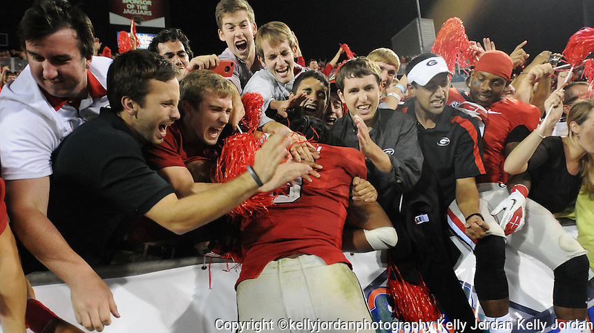 Kelly.Jordan@jacksonville.com--102712--Georgia fans surround player Alec Ogletree, (9), as he jumps into the crowd in the south end zone following their 17-9 win over the Gators during the annual Georgia-Florida football game at EverBank Field Saturday October 27, 2012 in Jacksonville, Florida.(The Florida Times-Union, Kelly Jordan)