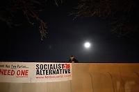 A member of Socialist Alternative hangs a banner outside a Rick Santorum campaign event at Jillian's, a bar in Manchester, New Hampshire, on Jan. 9, 2012.  Santorum is seeking the 2012 Republican presidential nomination.