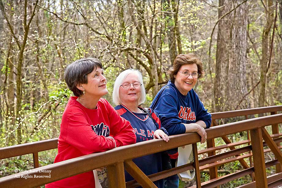 Three mature female friends wearing Ole Miss shirts rest on wooden country bridge in William Faulkner's Woods in Oxford, Mississippi