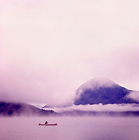 One Person canoeing in Red Canoe, in Early Morning Fog on Bowron Lake, Bowron Lake Provincial Park, BC, Cariboo Region of British Columbia, Canada