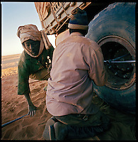 Sahara desert, Libya-Chad, November/December 2004..Every week, a convoy of 40 privately owned Libyan trucks loaded by the WFP with about 1000 metric tons of western food aid cross 2500 km of deep desert across Libya and Chad to reach more than 200 000 refugees from Darfur in camps near the Sudanese border. Abdallah, a Sudanese mechanic changes a wheel; punctures are extremely frequent, the trucks are loaded to the limit and some rocks are razor sharp...