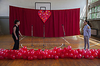 Serbia. Zitkovac is a village in Central Serbia situated in the municipality of Aleksinac, in the Nišava District. «Vuk Karadzic» Elementary School. School gym indoor. A teacher and a student are finishing event's preparation. Red inflated balloons and three microphones on stand. Red curtain and heart with colorful painted hands prints. 19.4.2018 © 2018 Didier Ruef