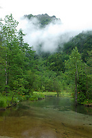 Clouds cling to the mountains around Kamikochi above the clear mountain stream that slows and deepens across the Kamikochi plain.