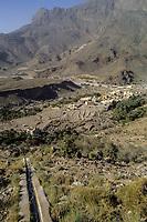 Wadi Bani Kharus, Oman.  Irrigation Canal (Falaj) Carries water down Mountainside to Village and date Palms below.