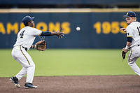 Michigan Wolverines second baseman Ako Thomas (4) tosses a ball to teammate Jack Blomgren (18) looks on against the Maryland Terrapins on April 13, 2018 in a Big Ten NCAA baseball game at Ray Fisher Stadium in Ann Arbor, Michigan. Michigan defeated Maryland 10-4. (Andrew Woolley/Four Seam Images)
