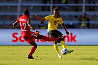 July 16th 2021; Orlando, Florida, USA; Jamaica midfielder Daniel Johnson passes the ball in front of Guadeloupe forward Dimitri Ramothe  during the Concacaf Gold Cup match between Guadeloupe and Jamaica on July 16, 2021 at Exploria Stadium in Orlando, Fl.