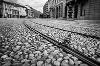 """Switzerland. Canton Ticino. Locarno. A pigeon on Piazza Grande. Derelict tram tracks. Due to the spread of the coronavirus (also called Covid-19), the Federal Council has categorised the situation in the country as """"extraordinary"""". It has issued a recommendation to all citizens to stay at home, especially the sick and the elderly. From March 16 the government ramped up its response to the widening pandemic, ordering the closure of bars, restaurants, sports facilities and cultural spaces. Only businesses providing essential goods to the population – such as grocery stores, bakeries and pharmacies – are to remain open. The town of Locarno is known for hosting the Locarno International Film Festival which takes place every year in August and involves open-air screenings at the main square, the Piazza Grande. 1.05.2020 © 2020 Didier Ruef"""