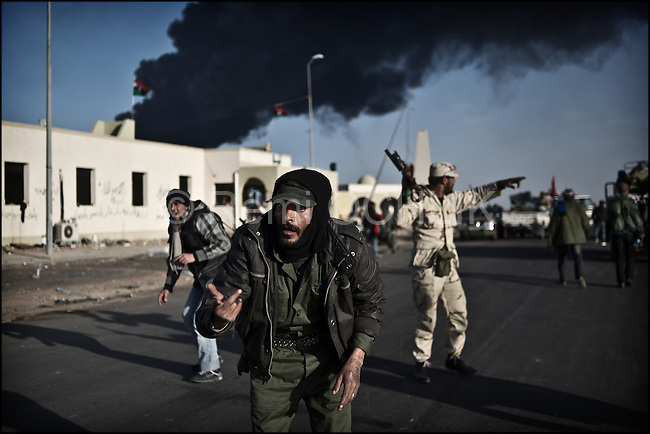 © Remi OCHLIK/IP3 -   RAS LANOUF March 11, 2011 - Rebel fighters start going away under bullet as the loyalist forces give the final assault...Opposition forces fight troops of colonel Muamar Gadhafi on a road just outside the strategic oil town of Ras Lanouf, Libya..Loyalist forces bombed the rebels from the air and the ground. At least five oppositin fighters were killed and fifteen injured