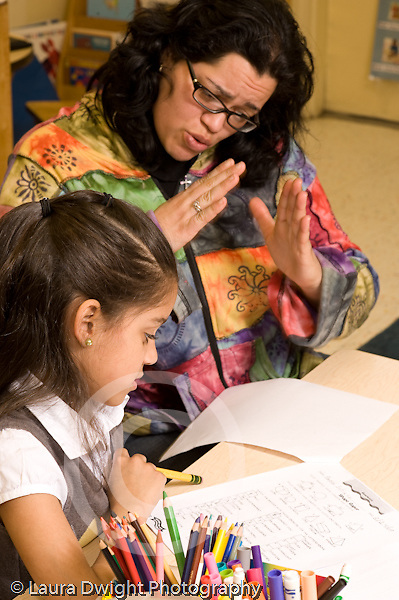 After school academic support program children in early primary grades: first and second grade, assisted by trained adults to finish homework female teacher workng with female student vertical