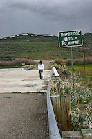 """Young woman walking away across bridge with sign """"The Bridge to No Where""""."""