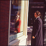 Woman sitting by window in cafe with man walking by outside
