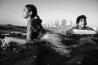 Gaza's only female surfers Abu Ganem and Rawan Abu Ganem look to the horizon in the Mediterranean Sea off Gaza City.