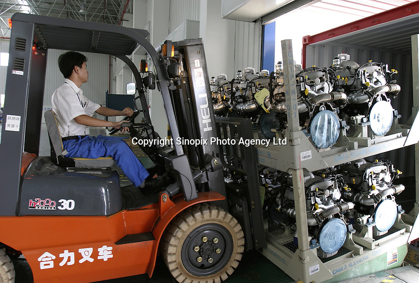 A Chinese General Motors employee operates a forklift to transport engines into a container destined for Canada at the Shanghai General Motors plant in Shanghai, China. The engines will be assembled on the GM model Equinox, which is a vehicle made of parts from around the world, very few of which are actually made in the USA..