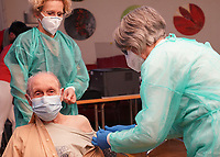 Gross-Gerau 27.12.2020: Erste Corona Impfung im Kreis Groß-Gerau<br /> Wendy Rushdan (MFA im MVZ, r) verabreicht Erwin Neumann die erste Dosis des COVID-19 Impfstoffs