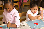 Preschool classroom 3-4 year olds art activity two girls gluing collages using opposite hands, gluing with paint brushes