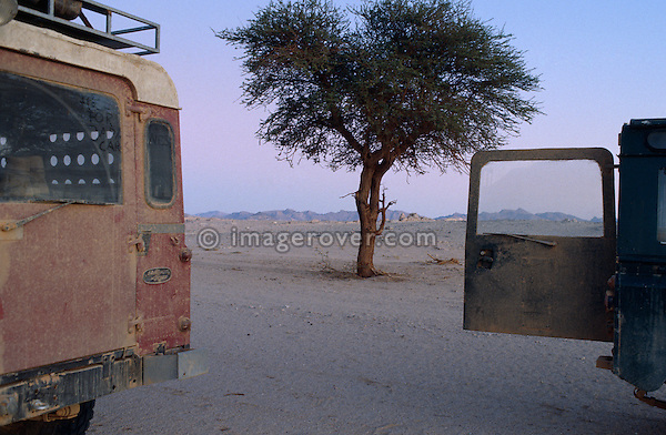 Africa, Algeria, Sahara Desert, nr. Amguid. Travellers, undertaking a sahara trip in their Series Land Rovers, stopping for an overnight stay after a day longs off road drive. --- No releases available, but release may not be required. Automotive trademarks are the property of the trademark holder, authorization may be needed for some uses.