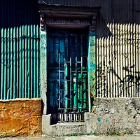 Paint-peeled doors are seen at the entrance to an unkept house, designed by using Spanish colonial architecture elements, built in a working class neighborhood of San Salvador, El Salvador, 15 November 2016.