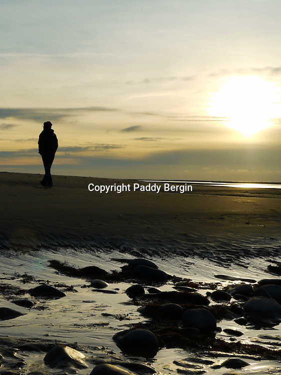 When the tide is low Ynyslas Beach is a vast expanse of sand and always provides wonderful views, shapes and patterns in the sand and reflections and colours as the sun sets.<br /> <br /> Stock Photo by Paddy Bergin