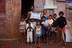 Family mother father with their seven children, standing outside their favela home holding portrait of children's grandparents urban poverty Brasilia Brazil South America 1980s