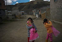 Leydi Jazmin Huaqui Gonzales, 9, left, and Sonia Rosemery Huaqui Gonzales, 8, right, play with their neighbors outside their homes in the Jose Carlos Mariategui neighborhood of Cerro de Pasco, Peru on June 17, 2013. All five of Sonia Gonzales' children have very high lead blood levels, including Gisella Pablo Gonzales, 13, 19.42 lead level; Leydi Jazmin Huaqui Gonzales, 9, 17.78; Sonia Rosemery Huaqui Gonzales, 8, 16.63; Luis Carlos Huaqui Gonzales, 6, 12.86 lead level; and Anthony Davis Huaqui Gonzales, 2, 12.30 lead level. In the background is a recent pile of mine tailings.