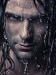 Man face with water running down it and wet long hair, artistic portrait with dramatic expression. Image © MaximImages, License at https://www.maximimages.com