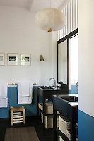 In this cool blue-and-white bathroom there are matching sinks with ample storage beneath in the shape of large wicker baskets